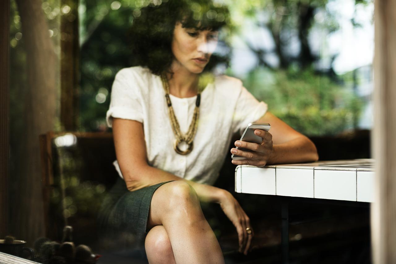 kobieta w depresji trzymająca w ręku smartfon
