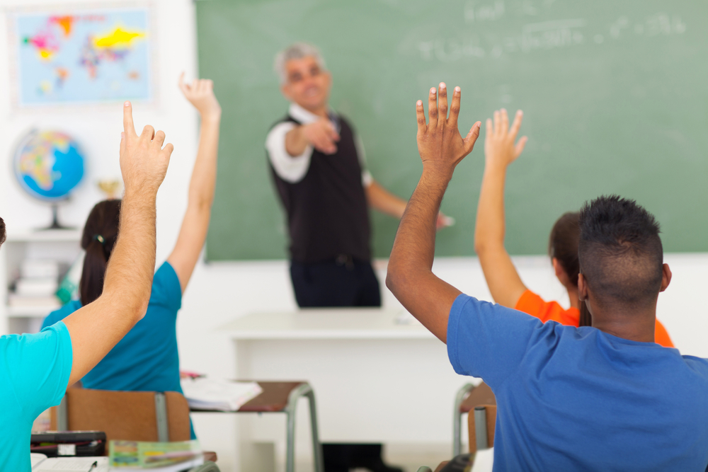 group of students with hands up in classroom during a lesson