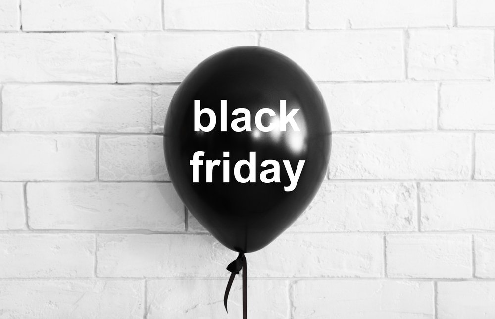 Black friday shopping. Black balloon with text on white bricks background, copy space