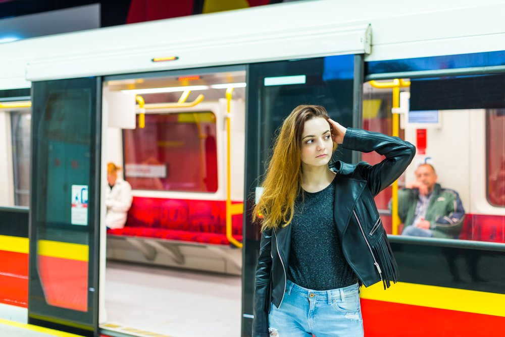 The girl near subway train at the metro station