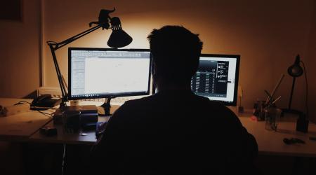 osoba siedząca przed monitorem komputera