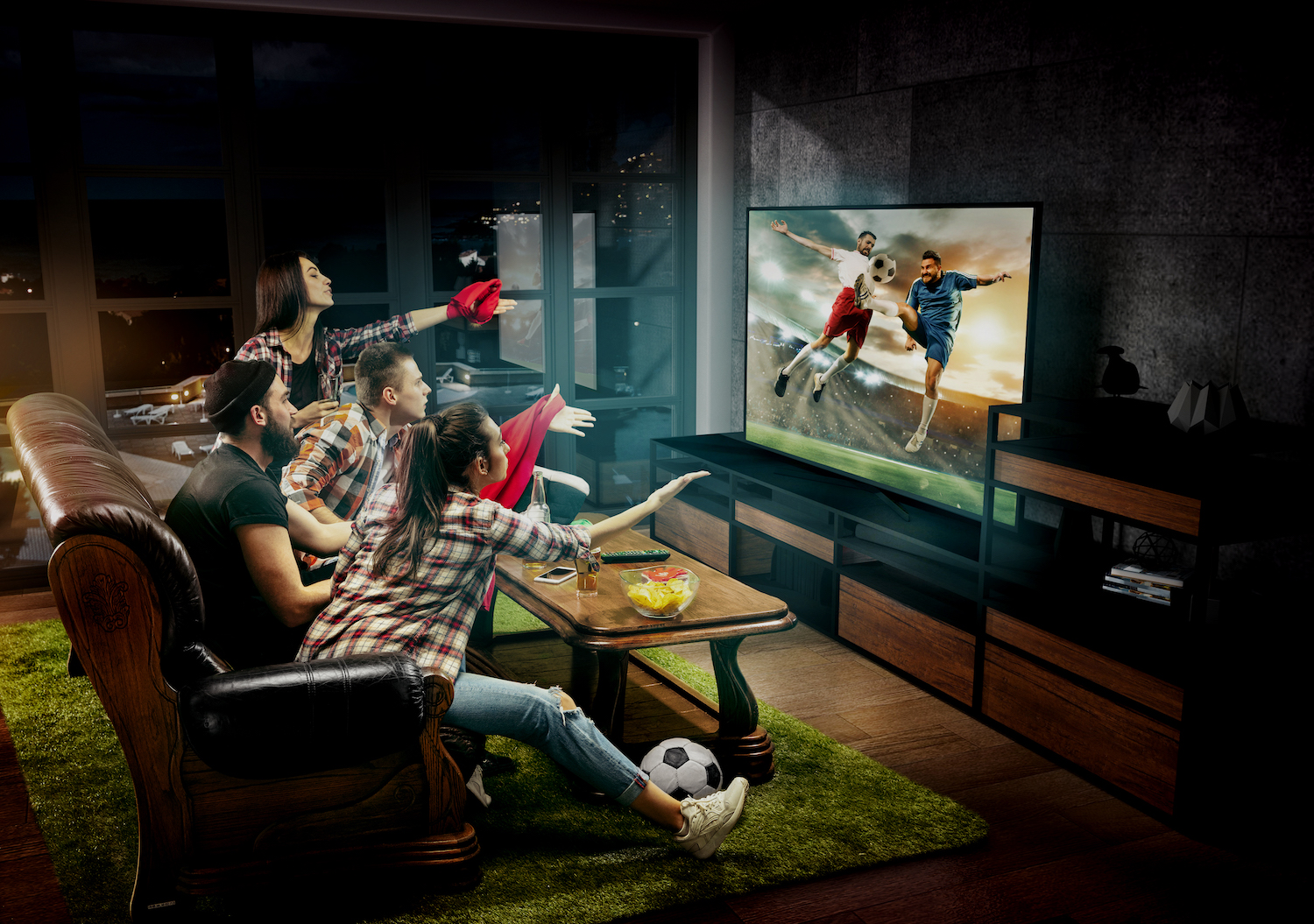 Group of friends watching TV, football match, sport together. Emotional men and women cheering for favourite team, look on goal and fighting for ball. Concept of friendship, leisure activity, emotions.