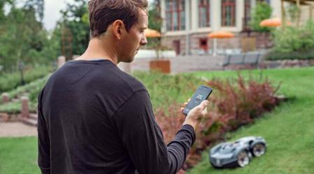 Mężczyzna korzystający z aplikacji do sterowania robotem koszącym